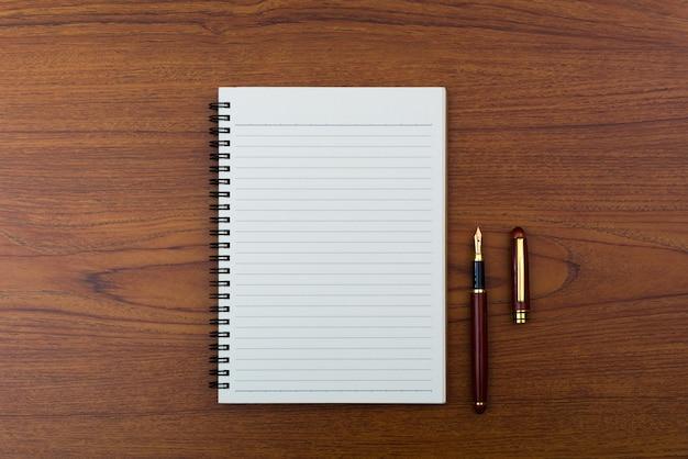 Füllfederhalter oder tintenschreiber mit notizbuchpapier auf holz