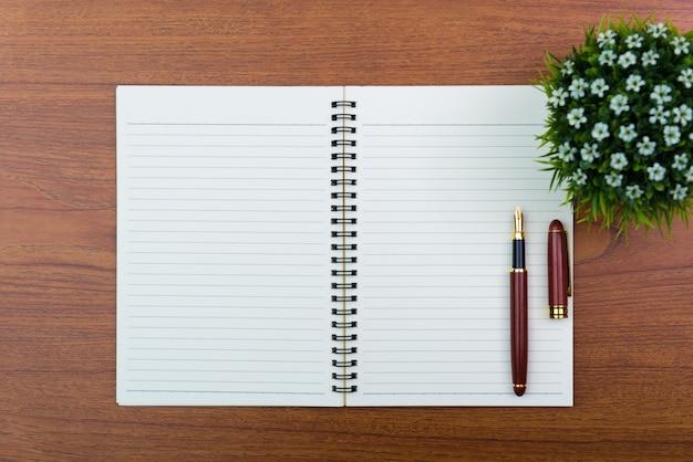 Füllfederhalter oder tintenschreiber mit notizbuchpapier und wenig dekorationsbaum