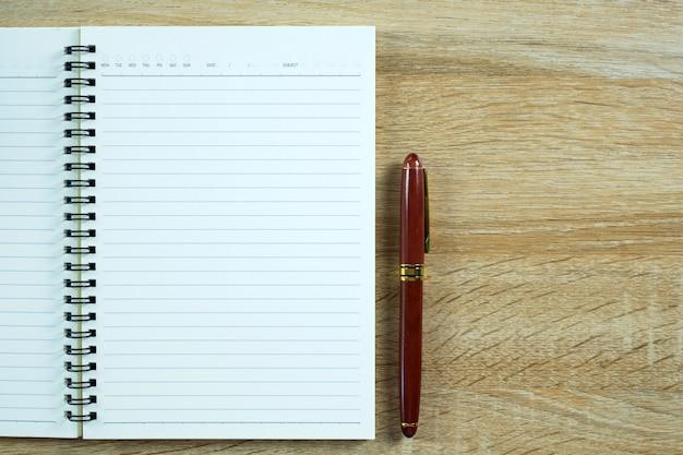 Füllfederhalter oder tintenstift mit notizbuchpapier auf hölzerner arbeitstabelle mit kopienraum