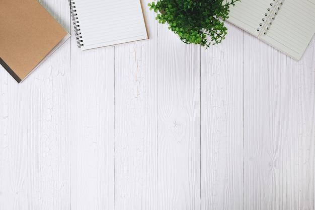 Füllfederhalter oder tintenstift mit notizbuchpapier und taschenrechner auf hölzernem arbeitstisch mit kopienraum