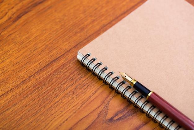 Füllfederhalter oder tintenstift mit notizpapier auf holz
