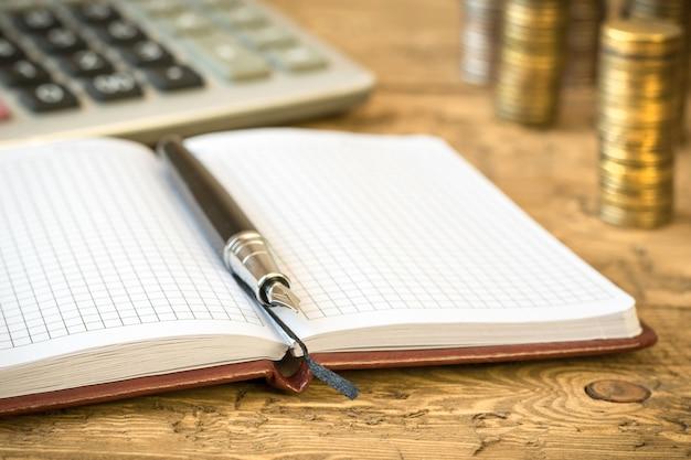 Füllfederhalter, taschenrechner, münzen und notizbuch auf einem holztisch.