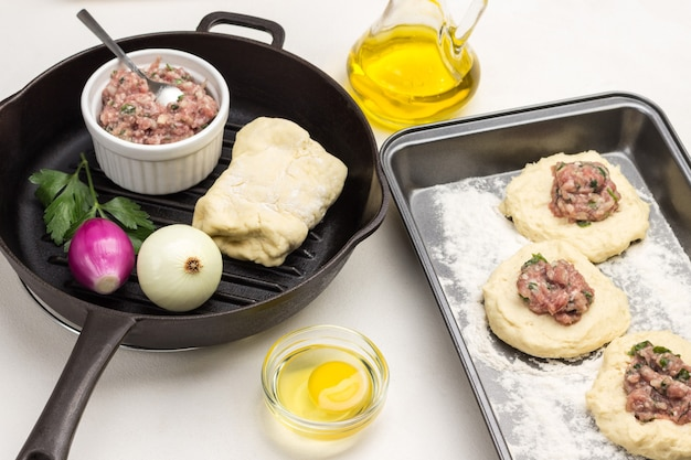 Füllung von fleisch auf rohen teigstücken auf backform. teig, hackfleisch und zwei zwiebeln in der pfanne anbraten. weißer hintergrund. ansicht von oben