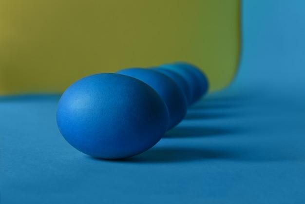 Fünf blau bemalte ostereier liegen diagonal auf einem blauen und gelben hintergrund