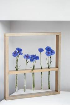 Fünf blaue schöne kornblumen in kleinen vasen in einem holzrahmen über grauem, einfachem blumengeschenk und dekoration am valentinstag
