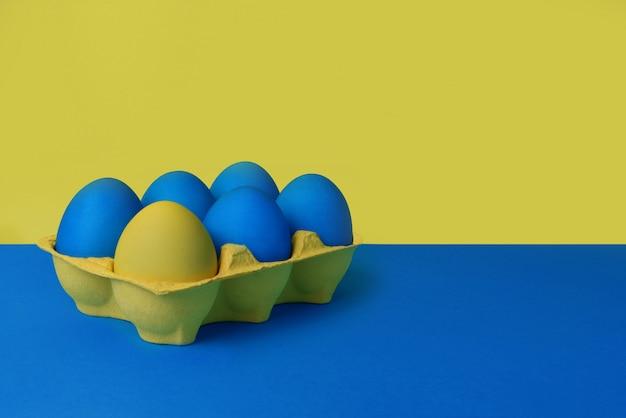 Fünf blaue und ein gelbes gemalte ostereier in der gelben verpackung auf blauem und gelbem hintergrund