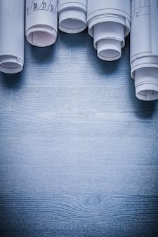 Fünf blaupausen auf blauem brett aufgerollt.