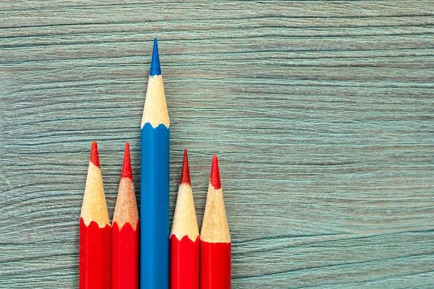 Fünf bleistifte unterschiedlicher länge, farbe eins blau lang, vier rot kurz auf türkisfarbenem naturholztisch hautnah. draufsicht. selektiver weichzeichner. . textkopierplatz.