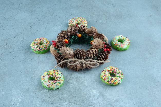 Fünf donuts um einen tannenzapfenkranz auf marmor.