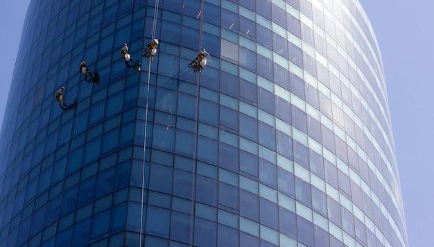 Fünf fensterputzer, die mit seilen außerhalb des modernen gebäudes aus blauem glas hängen riskante arbeit, gefährliche arbeit