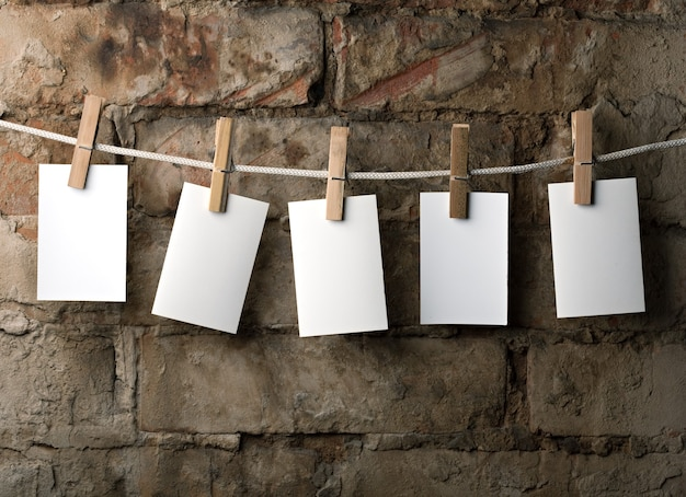 Fünf fotopapiere mit wäscheklammern auf backsteinhintergrund am seil befestigen