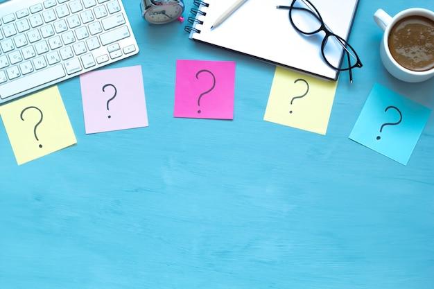 Fünf fragezeichen auf bunten aufkleberanmerkungen auf dem desktop. draufsicht platz kopieren.