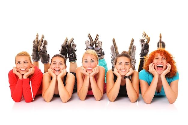 Fünf freundinnen ruhen auf weißem hintergrund mit ihren rollerblades an