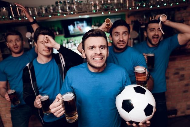 Fünf fußballfans sind traurig, dass ihre mannschaft in der bar verliert