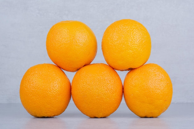 Fünf ganze köstliche orangen auf weißem hintergrund. foto in hoher qualität