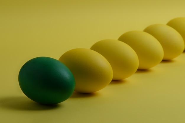 Fünf gelbe und ein grün gemalte ostereier liegen diagonal auf gelbem grund