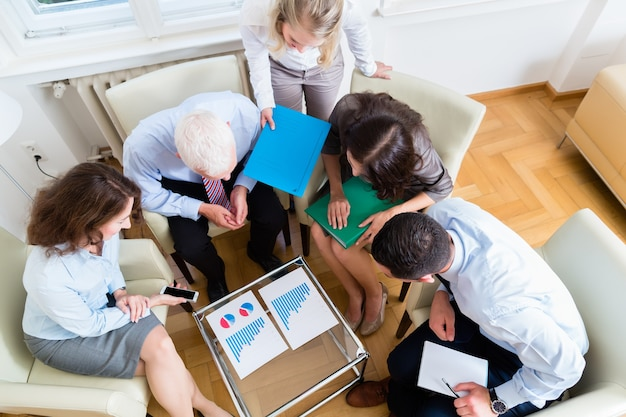 Fünf geschäftsleute als teambesprechung im büro, die grafiken und zahlen studieren