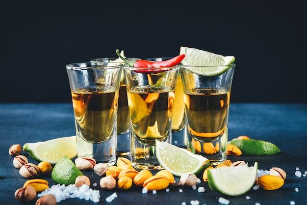 Fünf gläser alkohol mit snacks limette und pistazie, salz und chili-pfeffer zur dekoration. tequila-shots, wodka, whisky, rum
