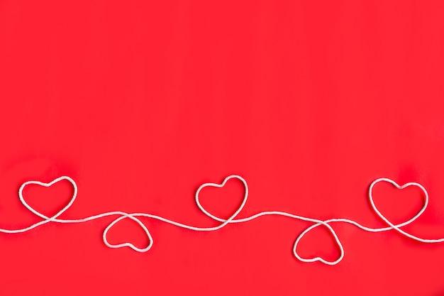 Fünf herzen aus weißem seil auf rotem hintergrund, draufsicht mit platz für text