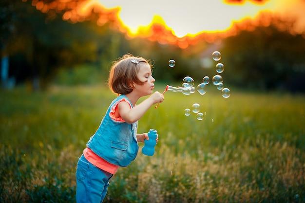 Fünf jahre alte kaukasische schlagseifenblasen des kindermädchens im freien bei sonnenuntergang.