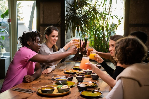 Fünf junge freunde stoßen auf einer dinnerparty an