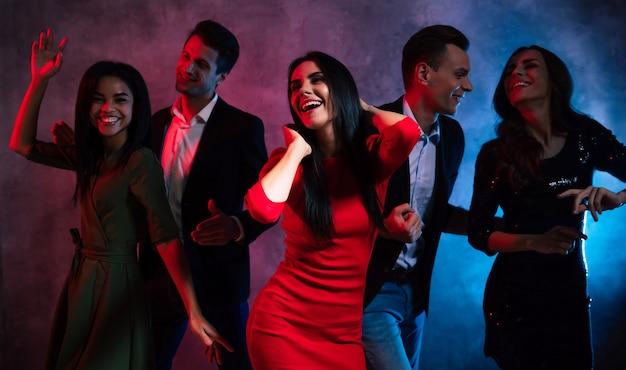 Fünf junge menschen unterschiedlicher geschlechter und nationalitäten tanzen gemeinsam mit erhobenen händen, lachen und amüsieren sich