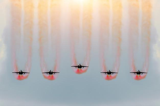 Fünf kampfjets fliegen zusammen mit rotem rauch.