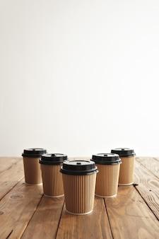 Fünf karton pappbecher mit schwarzen kappen in der reihe isoliert in der mitte des rustikalen holztischs