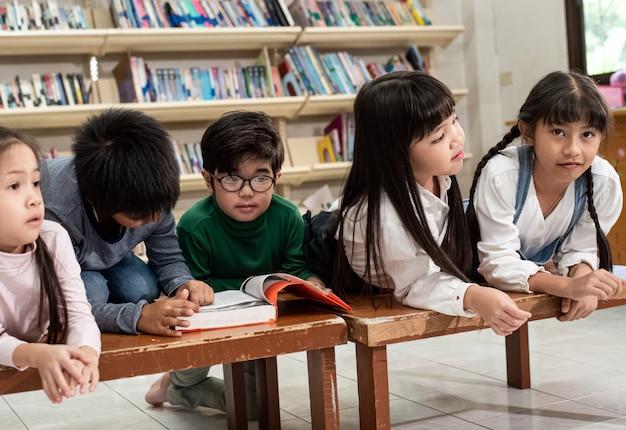 Fünf kleine kinder legen sich auf einen holztisch, spielen und treiben zusammen, glücklicher moment in der schule, verschwommenes licht