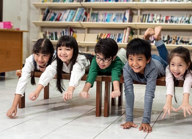 Fünf kleine kinder legen sich auf einen holztisch, spielen zusammen, heben die hände in die luft, fliegen wie ein flugzeug, glücklicher moment in der schule, verschwommenes licht