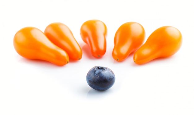 Fünf kleine reife orange traubentomaten und eine einzelne blaubeere lokalisiert auf weißem hintergrund. seitenansicht