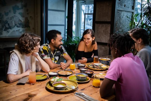 Fünf lächelnde studenten, die einen snack haben und in der college-kantine plaudern