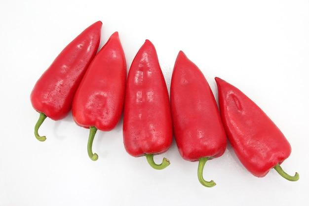 Fünf leuchtend rote paprika auf weißem grund