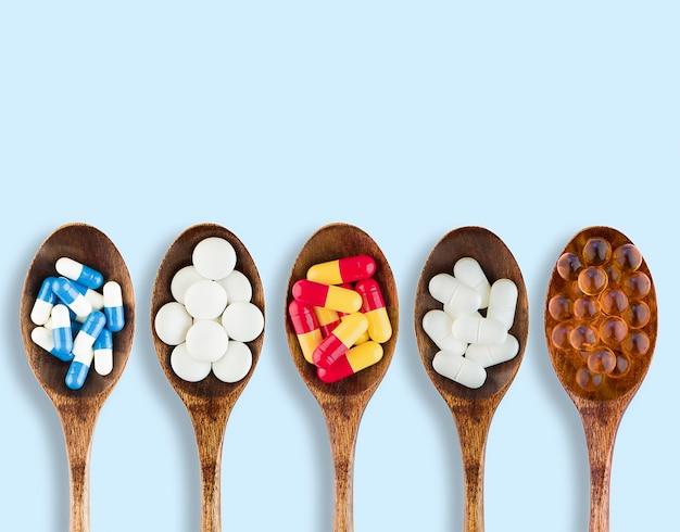 Fünf löffel mit verschiedenen pillen auf hellblauem hintergrund