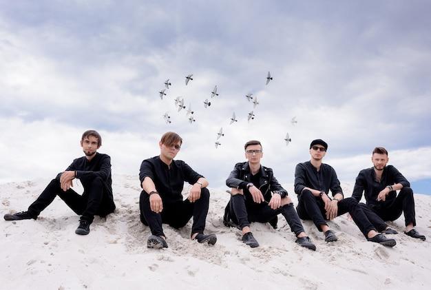 Fünf männer in schwarzer kleidung, die auf dem sandhügel sitzen und die kamera auf die fliegenden vögel im himmelshintergrund betrachten