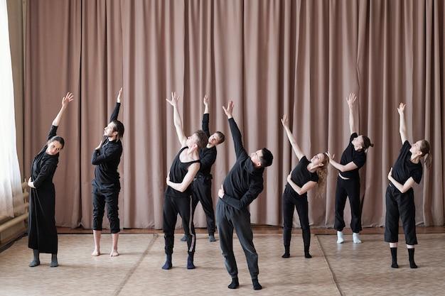 Fünf männer und drei mädchen in schwarzer aktivkleidung strecken einen arm nach oben, während sie während des trainings im studio auf dem boden stehen