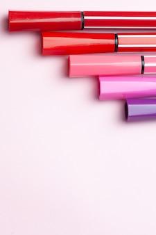 Fünf markierungen oder stifte in rosa, lila und rosa farbe liegen wie stufen auf einem rosa
