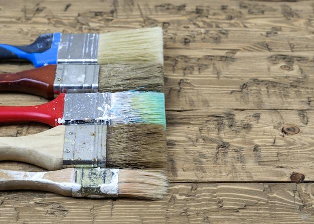 Fünf mehrfarbige bürsten auf einem rustikalen holztisch.