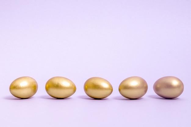 Fünf mit goldfarbe verzierte ostereier liegen in einer reihe vor einem lavendelhintergrund. konzept für ostern, frühling. selektiver fokus. speicherplatz kopieren.