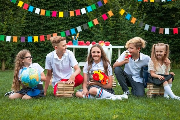 Fünf niedliche kinder mit büchern, globus und blumen, die auf grünem gras gegen flaggenhintergrund sitzen