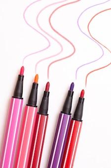 Fünf offene markierungen oder stifte in pink, lila, pink auf weiß