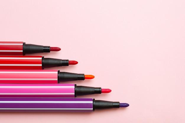 Fünf offene markierungen oder stifte in rosa, lila und rosa farbe liegen wie stufen auf einem rosa