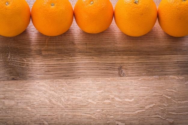 Fünf orangen in reihe auf holzbrett organisiert