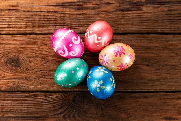 Fünf ostereier in trendigen farben, klassisch blau, grün, orange, magenta und golden, dekoriert auf einem alten holztisch.