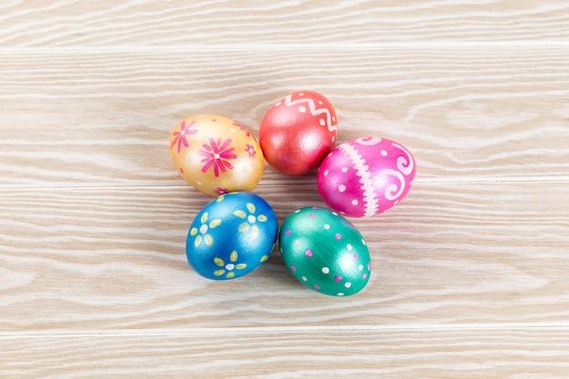 Fünf ostereier in trendigen farben, klassisch blau, grün, orange, magenta und golden, dekoriert auf weißem holztisch.