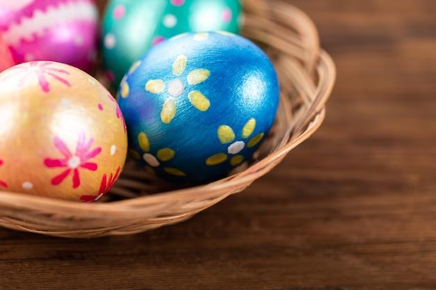 Fünf ostereier in trendigen farben, tiefblau, grün, orange, magenta und golden, dekoriert im korb auf altem holztisch.