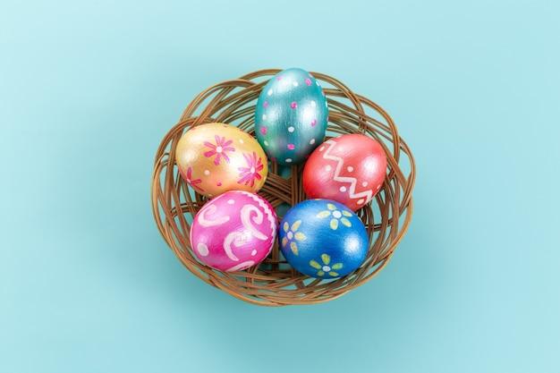 Fünf ostereier in trendigen farben, tiefblau, grün, orange, magenta und golden, dekoriert im korb auf blau