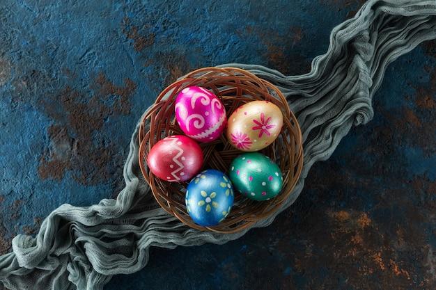 Fünf ostereier in trendigen farben, tiefblau, grün, orange, magenta und golden im korb verziert