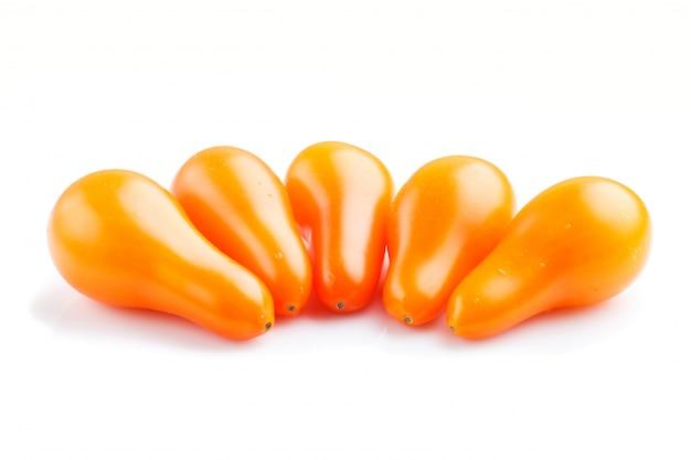 Fünf reife orange traubentomaten lokalisiert auf weißem hintergrund. seitenansicht.
