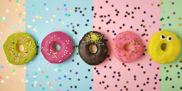 Fünf runde donuts mit verschiedenen füllungen und streuseln